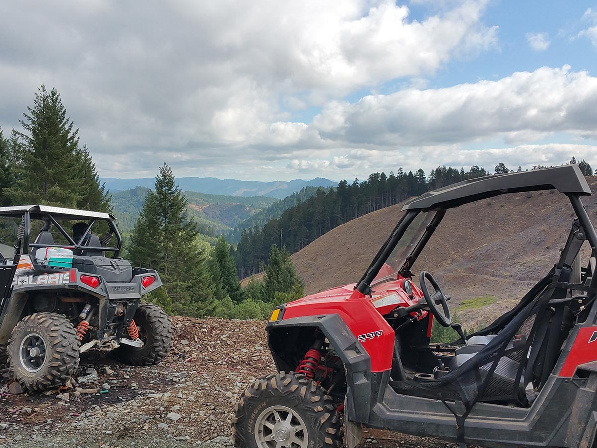 Two Polaris Rzr off-road vehicles sit atop a mountain on a day with scattered clouds in background