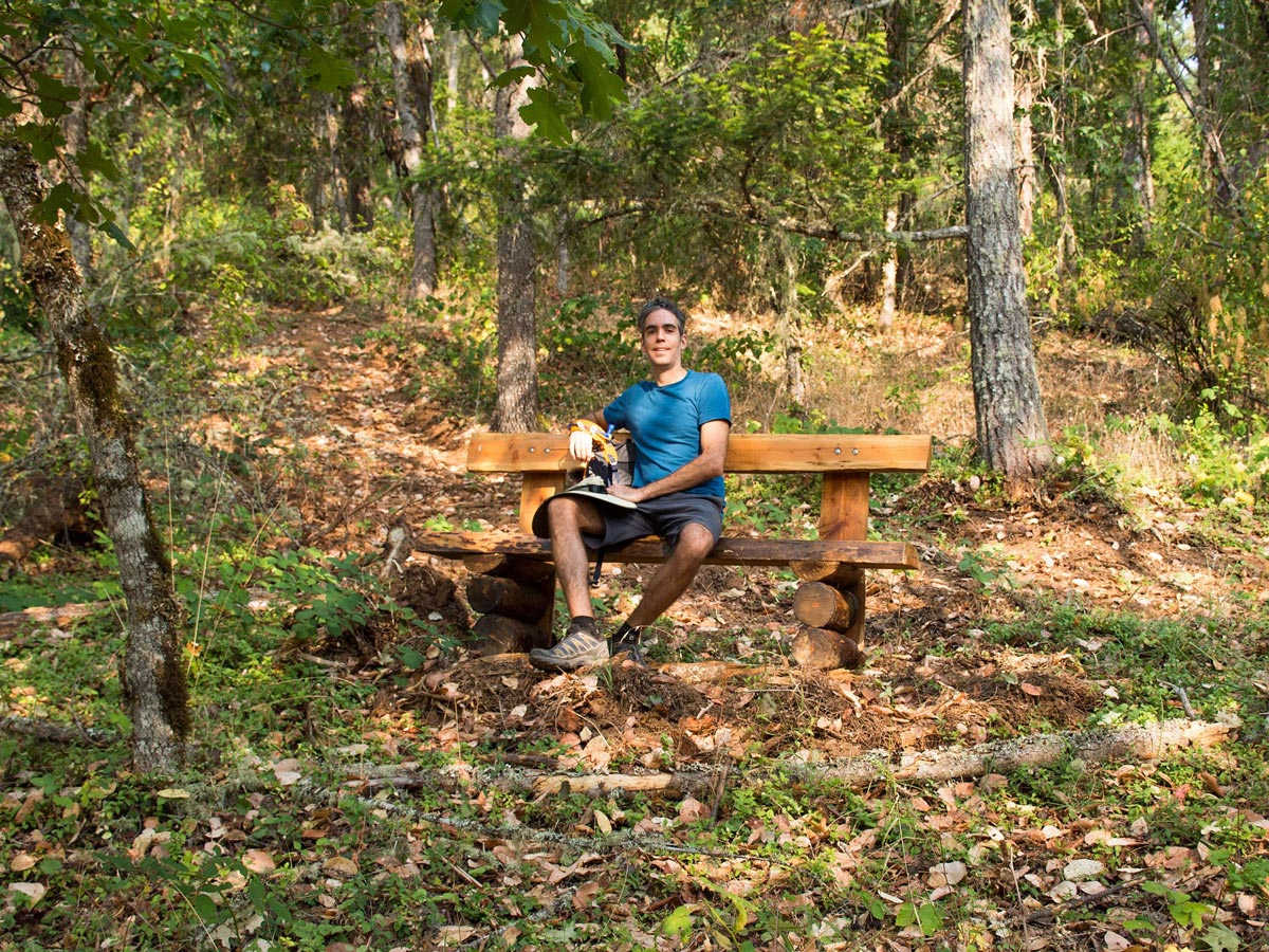 A hiker takes a break on a secluded bench within a forest