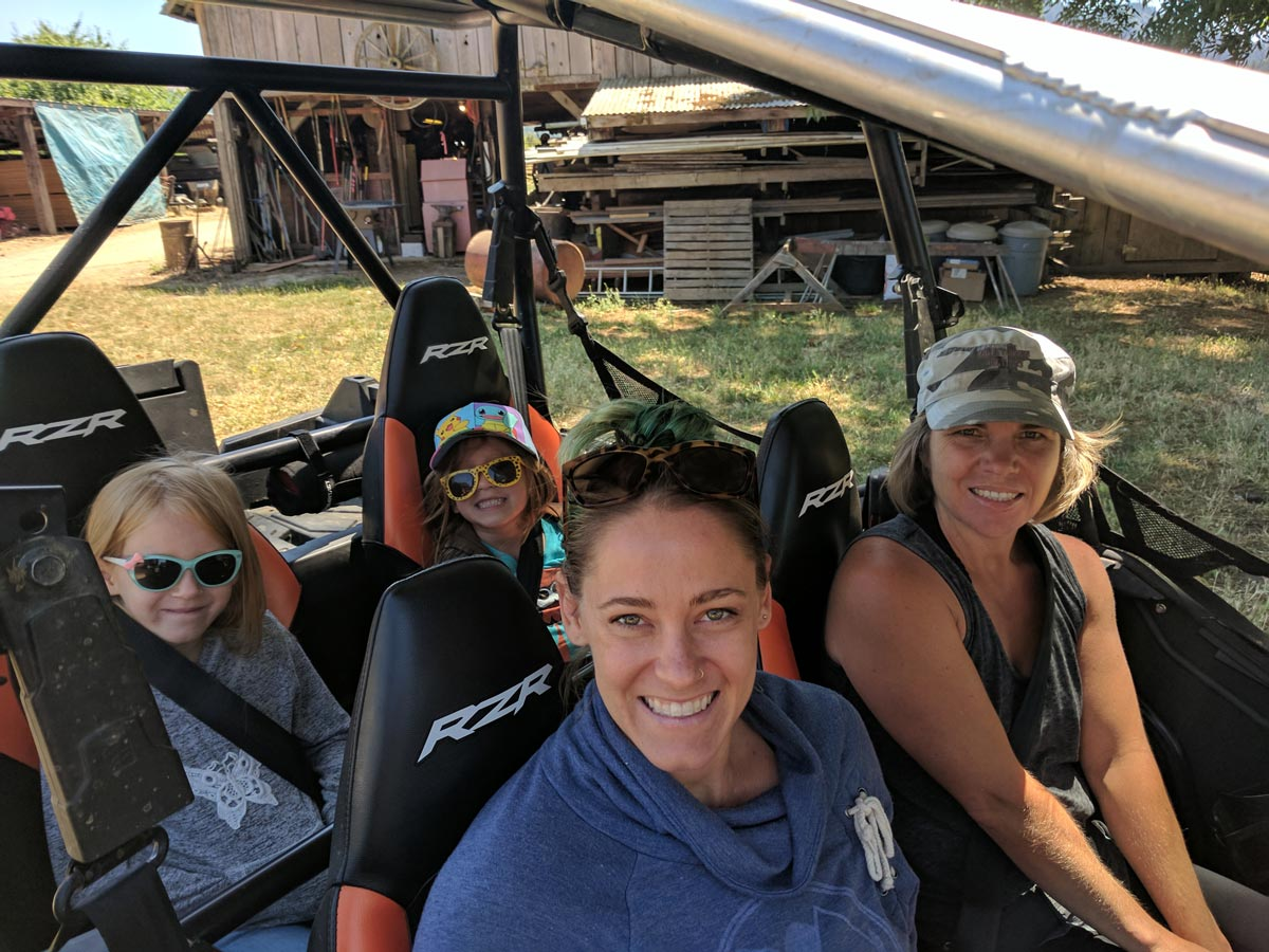 Two women and two girls sit inside a Polaris Rzr off-road vehicle and smile at the camera