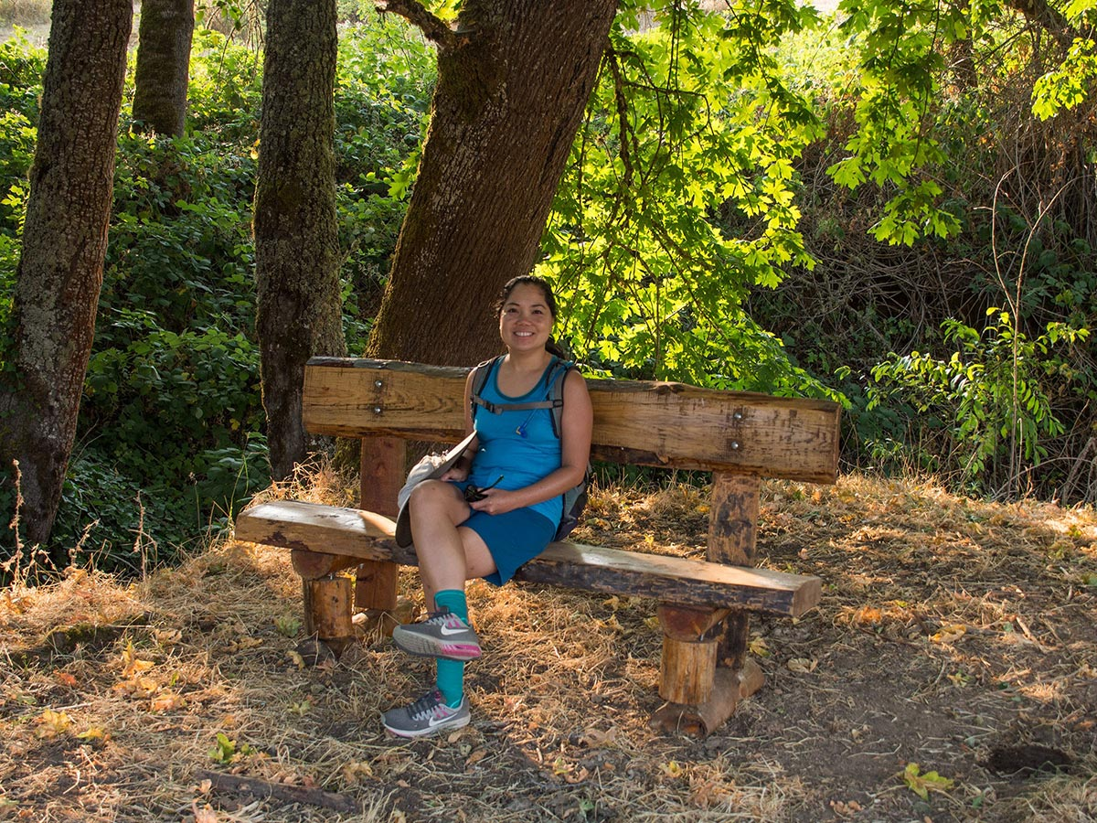 A woman sits on a bench in a heavily forested section of a trail