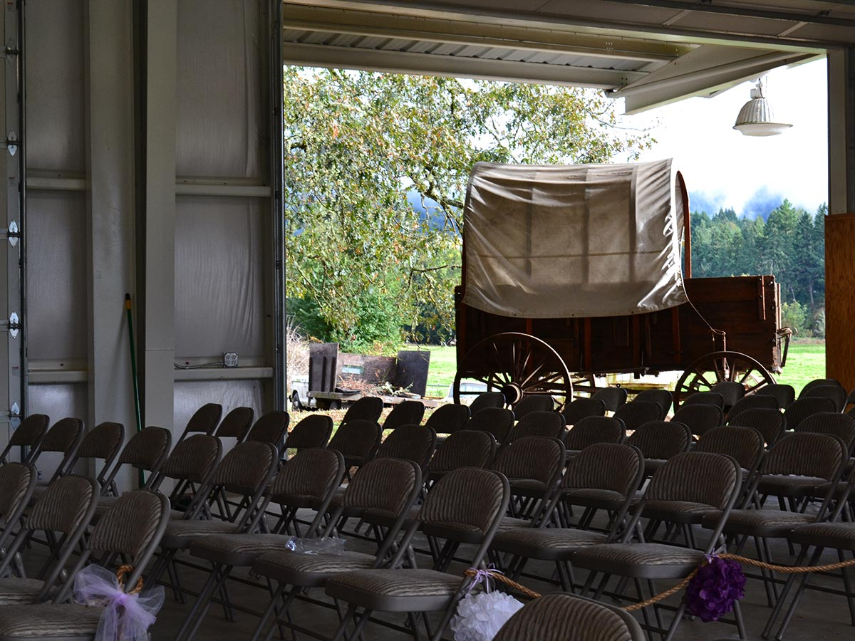 An industrial is set up as a meeting facility with folding chairs and a covered wagon in back