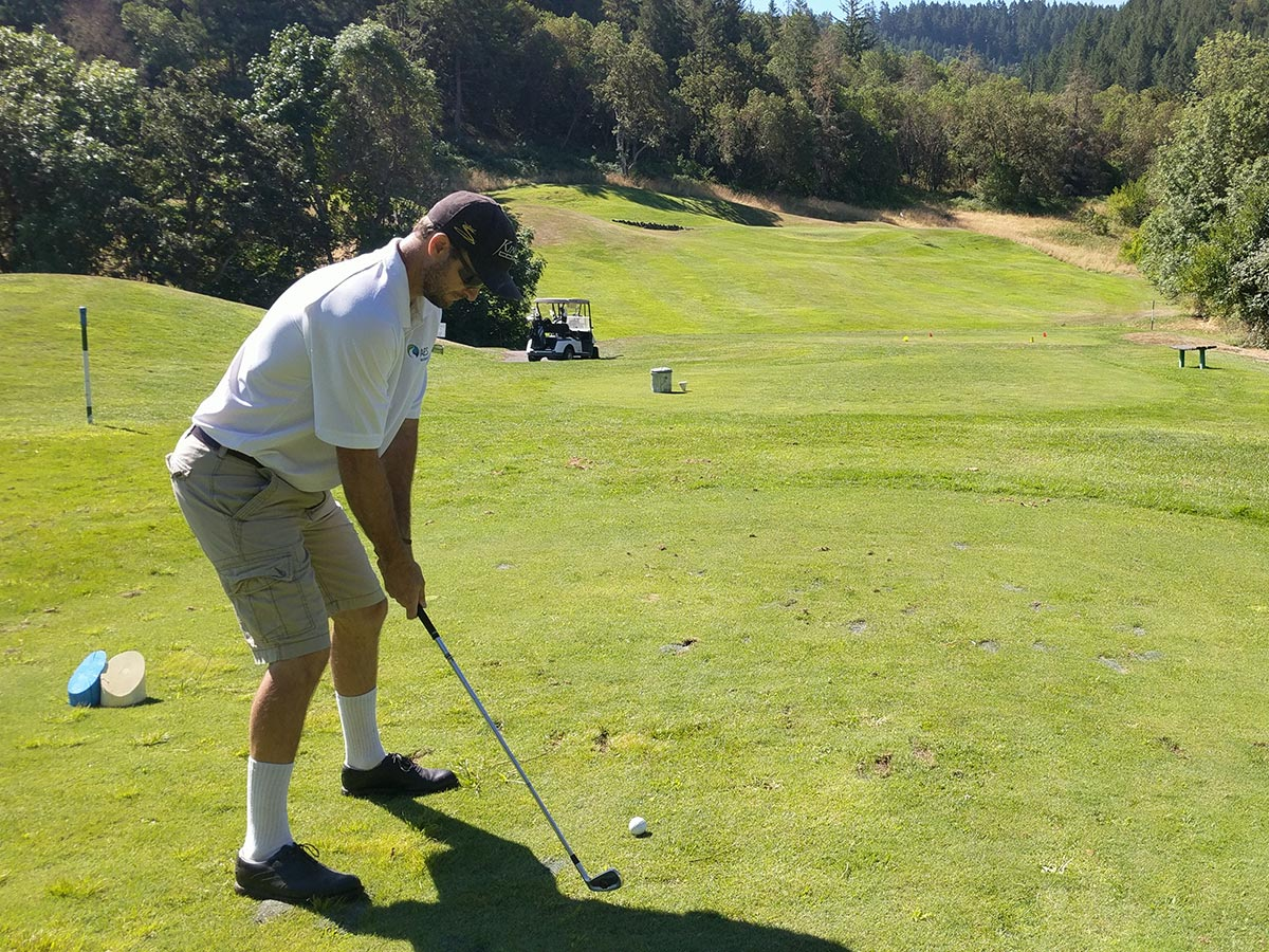 A young man tees off on a par three mountain golf hole