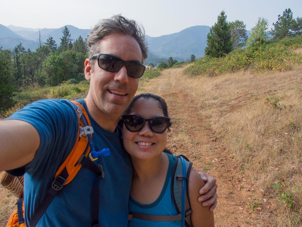 A couple stands arm in arm and takes a selfie while hiking a prairie trail