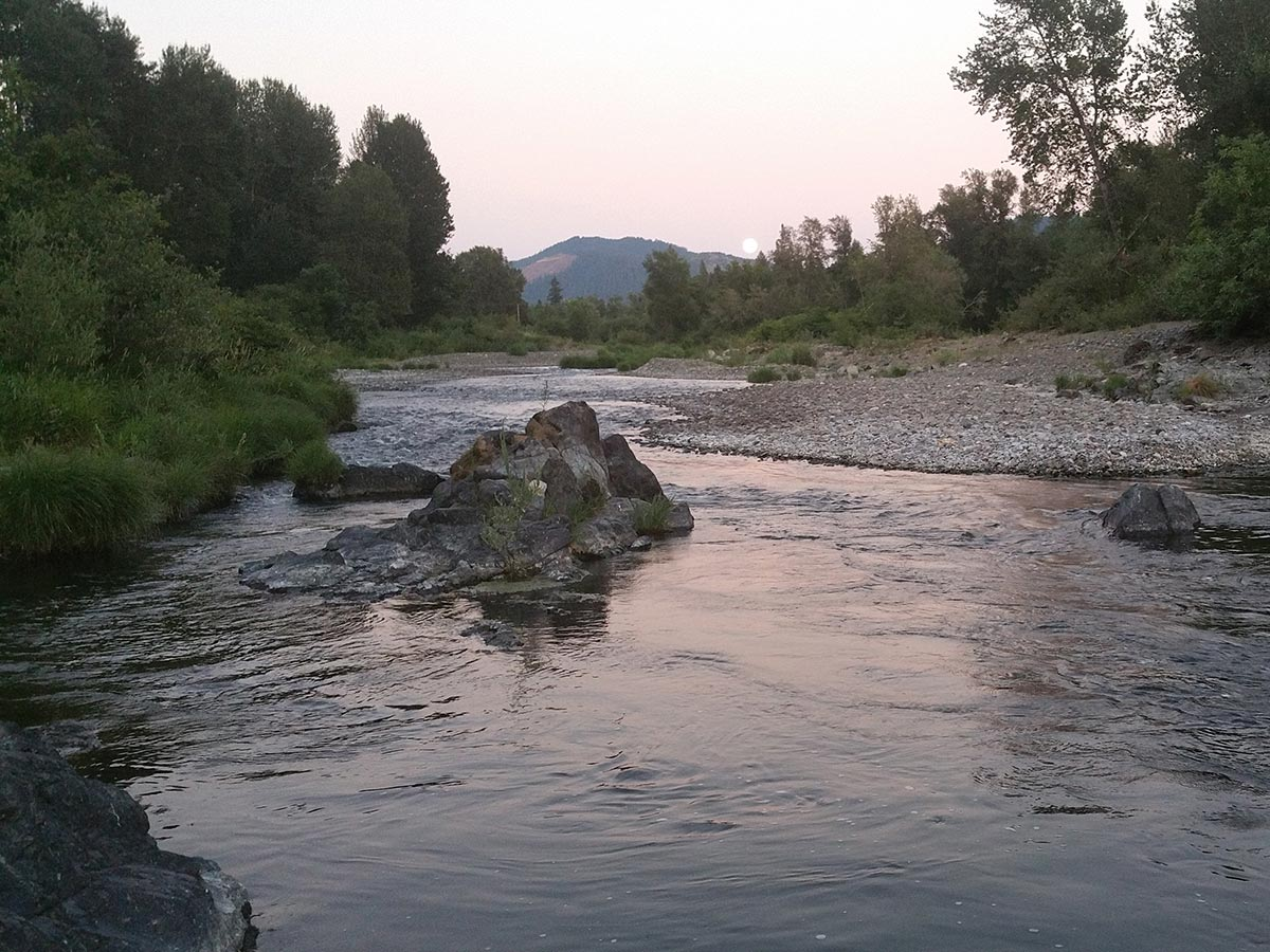 A river rolls quietly half-lit in the evening light