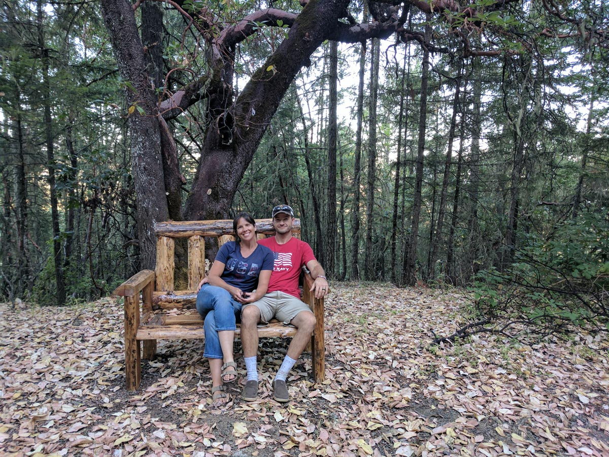 A couple sits on a log bench in a forested copse