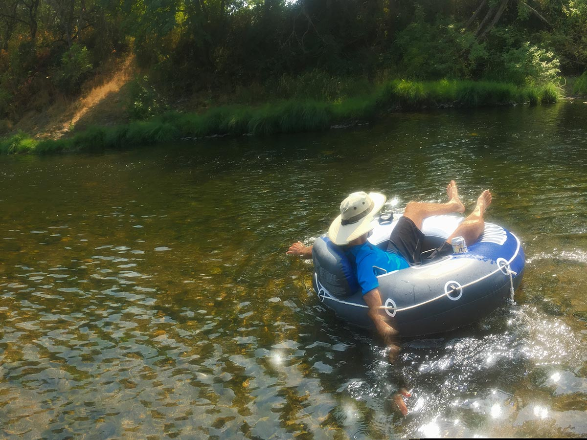 A man wearing a sun hat rides an inner tube down a lazy river