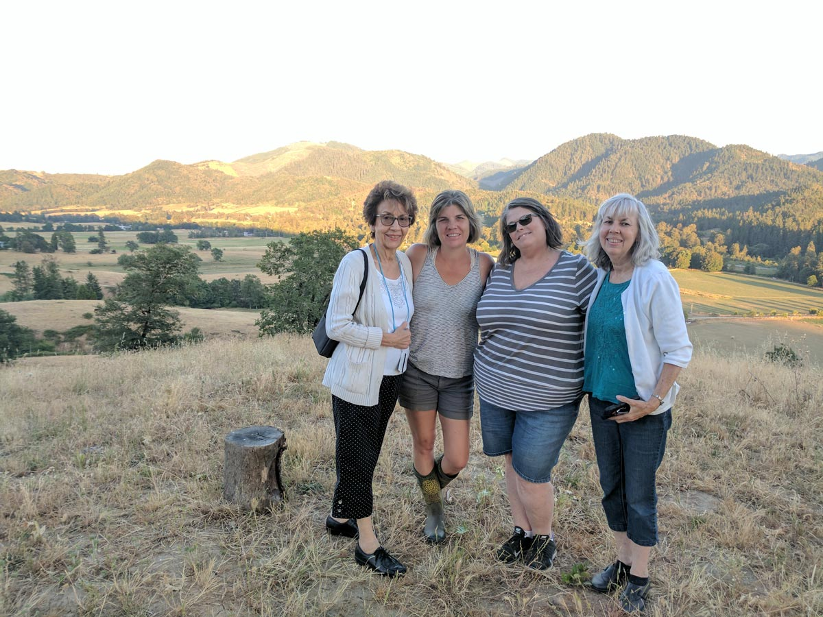 Four women pose at the top of hill overlooking a beautiful valley