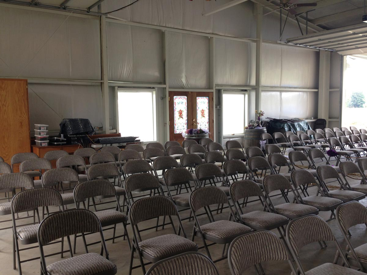 An industrial barn is set up for meetings and includes a sound system